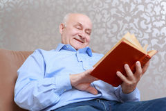 Man reads a book at home. Exciting story. Smiling elderly man reading a book while sitting in her living room in an armchair Royalty Free Stock Photo