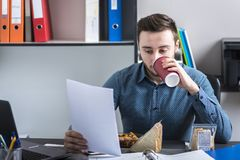 The man reads documents and drinks coffee. During a meal break Royalty Free Stock Images