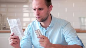 A man reads the instructions for taking pills.  stock footage