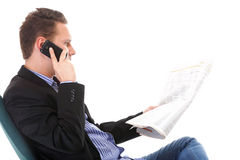 Man reads newspaper phoning - economy news Stock Images