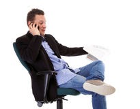 Man reads newspaper phoning - economy news Royalty Free Stock Images