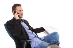 Man reads newspaper phoning - economy news Stock Image
