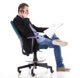Man reads newspaper phoning - economy news Stock Photo
