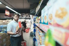 A man reads the product on a package when shopping in a supermarket. A man dies out food at the store.  Stock Photo