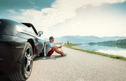 Man reads roads map sitting near his cabriolet royalty free stock image
