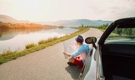 Man reads roads map sitting near his cabriolet on picturesque mo. Untain road stock photography