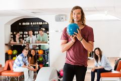 Man Ready With Bowling Ball in Club. Young men ready with bowling ball with friends in background at club Royalty Free Stock Image