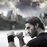 Man ready to fight. Retro styled photo of a young sexy man with fists up ready to fight against city background and dramatic sky Stock Photos