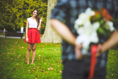 Man ready to give flowers to girlfriend Royalty Free Stock Image
