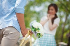 Man ready to give flowers to girlfriend Stock Image