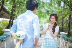 Man ready to give flowers to girlfriend. In the park Royalty Free Stock Photography
