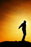 Man ready to jump. Adult crazy man is jumping on colorful sky background.Silhouette of man and beautiful sunset sky. Royalty Free Stock Photography