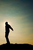 Man ready to jump. Adult crazy man is jumping on colorful sky background.Silhouette of man and beautiful sunset sky. Stock Photo