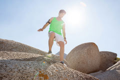 Man ready to jump from rock. On a sunny day Royalty Free Stock Photo