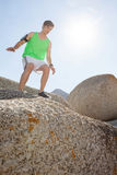 Man ready to jump from rock. On a sunny day Royalty Free Stock Photography