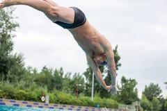 Man ready to jump on staring block at swimming pool. Swimmer on starting block at public swimming pool Royalty Free Stock Image