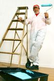Man ready to paint. A senior man with a paint roller and ladder ready to paint Royalty Free Stock Photography
