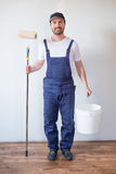Man ready to paint one wall holding painting tool. Man ready to paint a wall holding painting tools royalty free stock photos