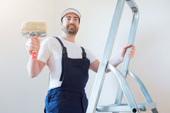 Man ready to paint one wall holding tools. Man ready to paint a wall holding painting tools royalty free stock image
