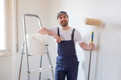 Man ready to paint one wall holding painting tools. Man ready to paint a wall holding painting tools stock photography