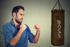 Man ready to punch boxing bag with boss written on it. Employee employer relationship concept. Man ready to punch boxing bag with word boss written on it Stock Photography