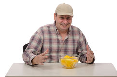 A man is ready to taste the yellow watermelon. A countryman in a baseball cap is ready to taste the yellow watermelon on a white background Royalty Free Stock Photo