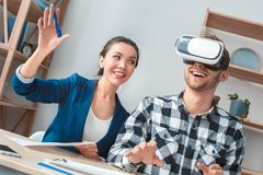 Man at real estate agency sitting in virtual reality headset agent showing customer offer cheerful royalty free stock images