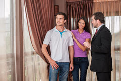 Man real estate agent showing couple new house. Royalty Free Stock Photos