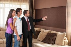 Man real estate agent showing couple new house. Stock Images