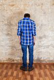 Man Rear View. Rear View of the Sad Young Man by the Old Wall Royalty Free Stock Image
