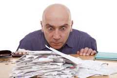 Man and receipts. Heap of receipts and terrified man Royalty Free Stock Images