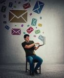 Man receive a lot of different messages coming out of notebook screen royalty free stock photo