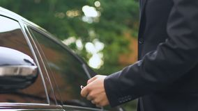 Man receives keys to luxury auto from dealer in salon, test drive, close up. Stock footage stock video