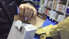The man receives the parcel at indoor the post office. Mail international unpacking parcels online trading stock video
