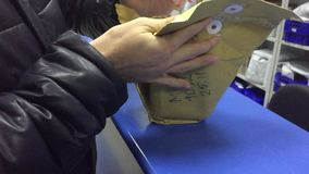The man receives the parcel at the post office. Mail international unpacking parcels online trading indoor stock video