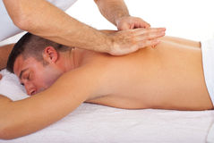 Man receiving back massage. Man relaxing with a back massage at spa retreat Royalty Free Stock Photos