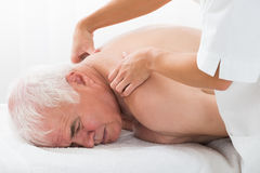 Man Receiving Back Massage. Close-up Of A Senior Man Receiving Back Massage In Spa Stock Photo