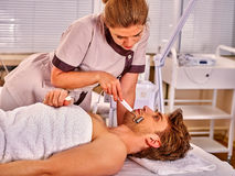 Man receiving electric facial peeling hydradermie massage. Royalty Free Stock Images
