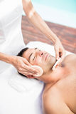 Man receiving a facial massage from masseur. In spa royalty free stock images