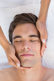 Man receiving facial massage at spa center Stock Images