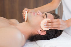 Man receiving facial massage at spa center Stock Photos