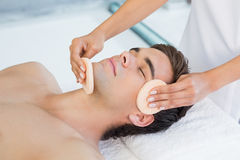 Man receiving facial massage at spa center Stock Images