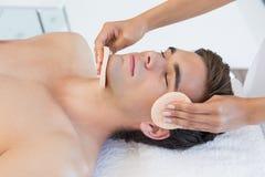 Man receiving facial massage at spa center Stock Image