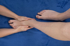 Man receiving a foot massage by a female masseur. Stock Images