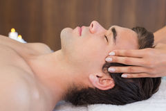 Man receiving head massage at spa center Stock Photo