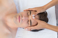 Man receiving head massage at spa center Stock Photos