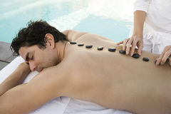 Man Receiving Hot Stone Massage By Pool Royalty Free Stock Photography