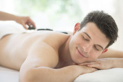 Man Receiving Hot Stone Therapy At Spa. Relaxed young men receiving hot stone therapy at health spa Royalty Free Stock Images