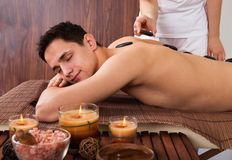 Man receiving lastone therapy in spa Stock Photography