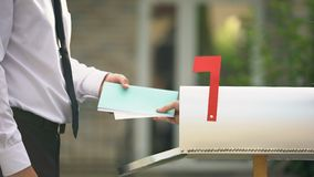 Man receiving letters and bills in mailbox in front of house, mail delivery. Stock footage stock video